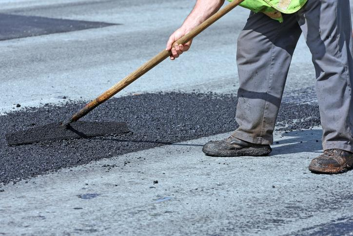 Spreading Hot Asphalt On A Pothole Repair Site